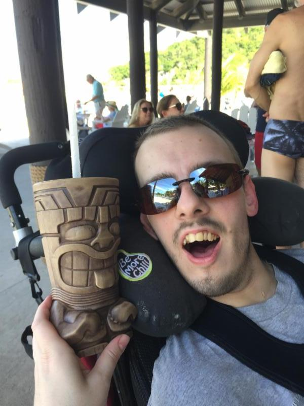nick smiling wearing dark sunglasses with a tiki cup next to him.