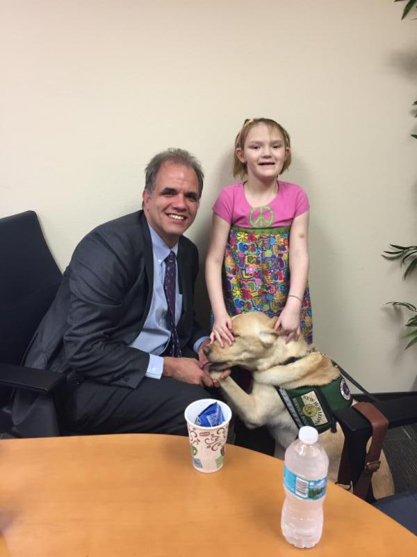 Matt sitting next to Kailea and her service dog.