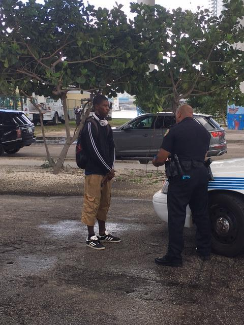 police officer speaking with a young man at a park.