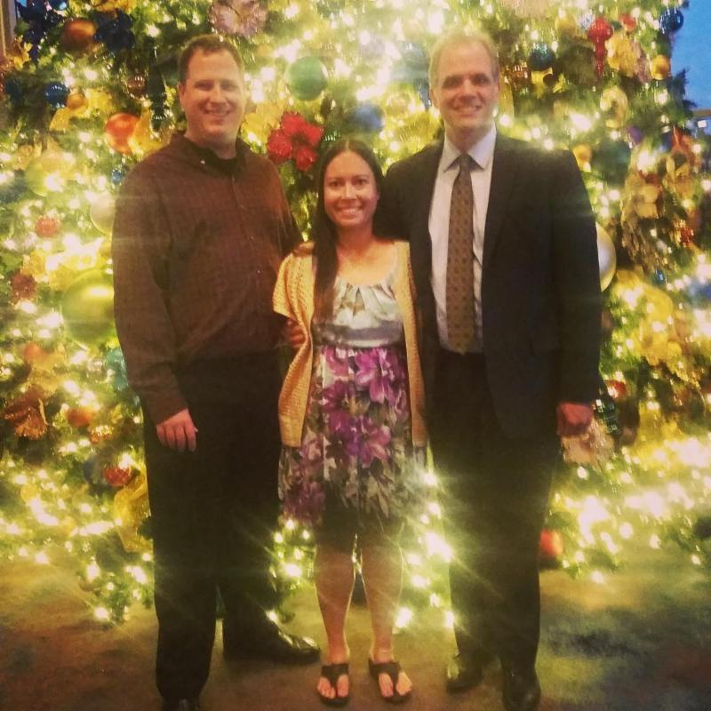 Matt, his client and her husband standing in front of a Christmas tree.
