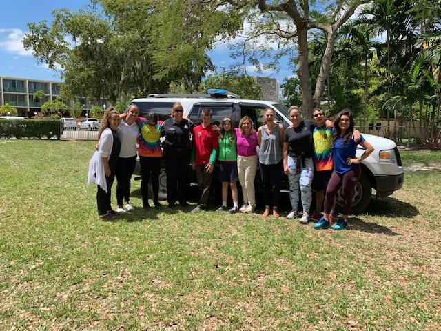 group picture in front of a police vehicle at crystal academy with debbie officer denham and the crystal academy students