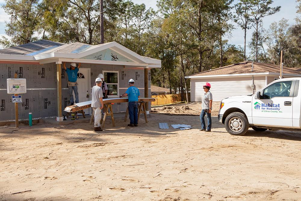 house under construction with a habitat for humanity pick up truck in front of the house and construction workers