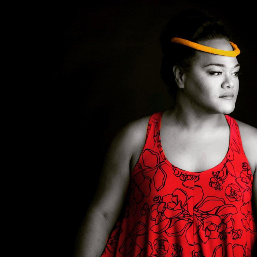 Black and white image of Kaumakaiwa Kanaka'ole with red dress.