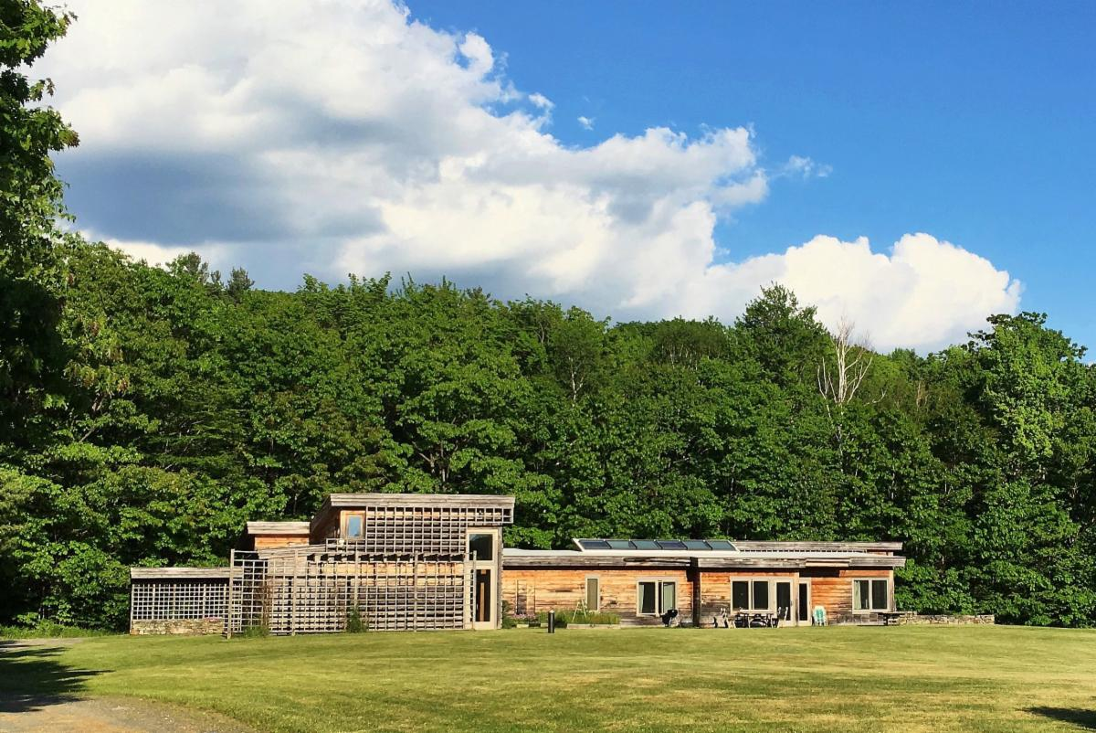 A long one story brown wooden building sits in a grassy clearing with a backdrop of trees. Modern in architecture, the building has a second story bump up on the left end.