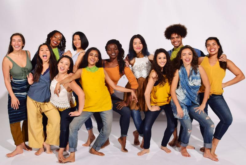 A large group of dancers in casual clothes and barefoot, stand against a white background.