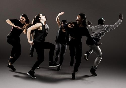 Six dancer, all dressed in black and grey street clothes, dance against a grey background.