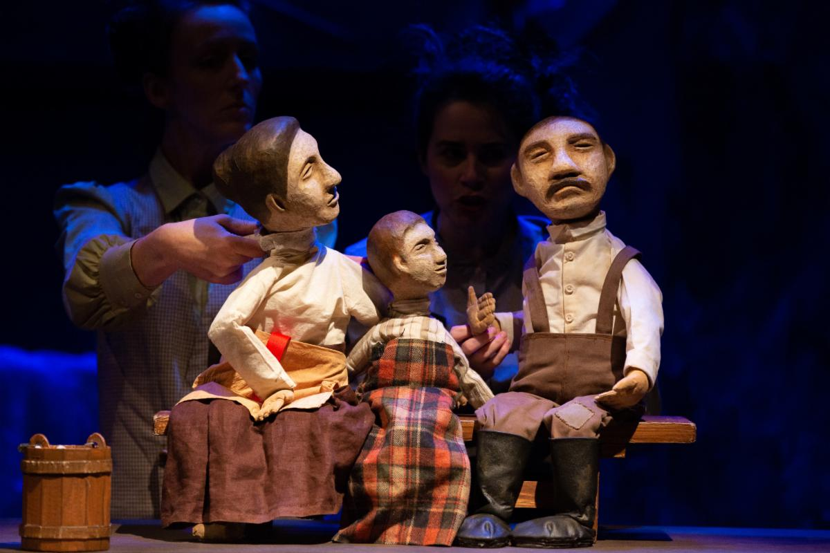 Three puppets - a mother, child, and father - sit on a bench.  They are dressed in clothes of the 1900's. The puppetmasters are barely visible behind them.