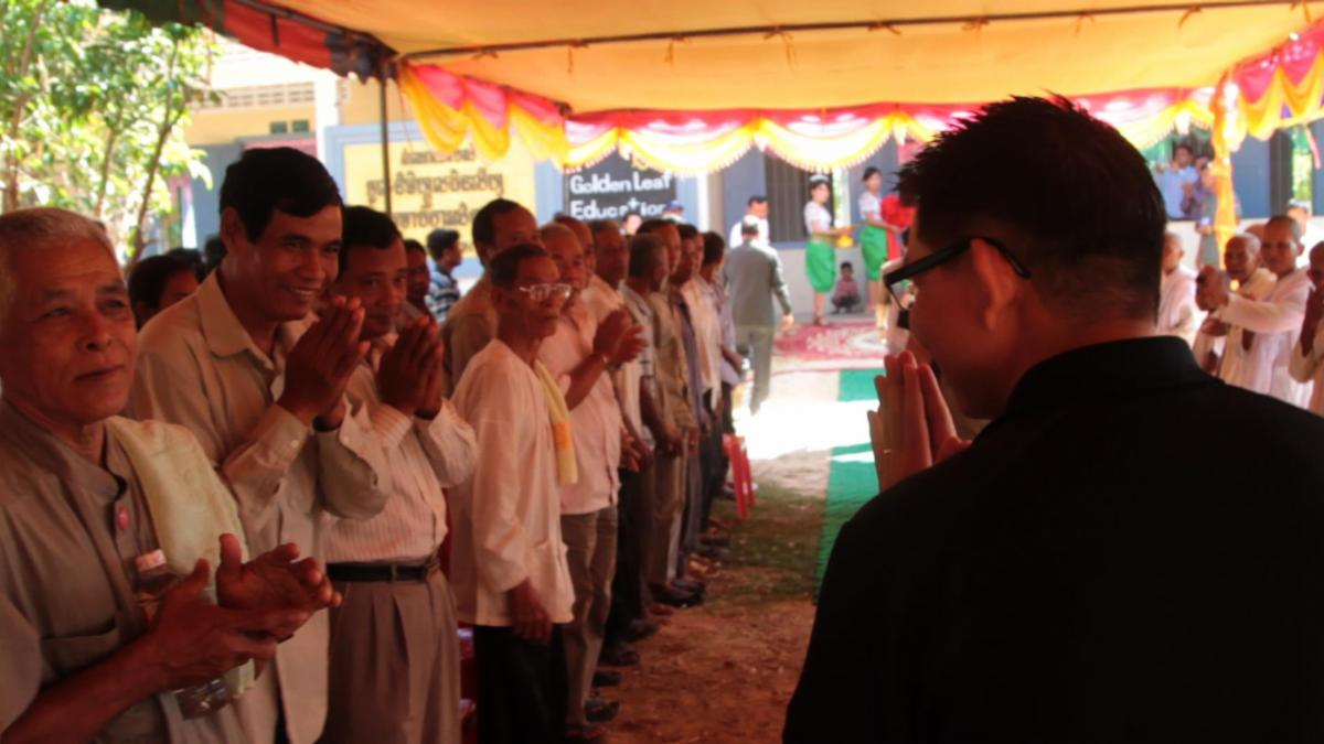 Film sill from Risking Light. A long line of people stand to the left under a yellow tent.  A man stands with his back to the camera right and makes wai bow.