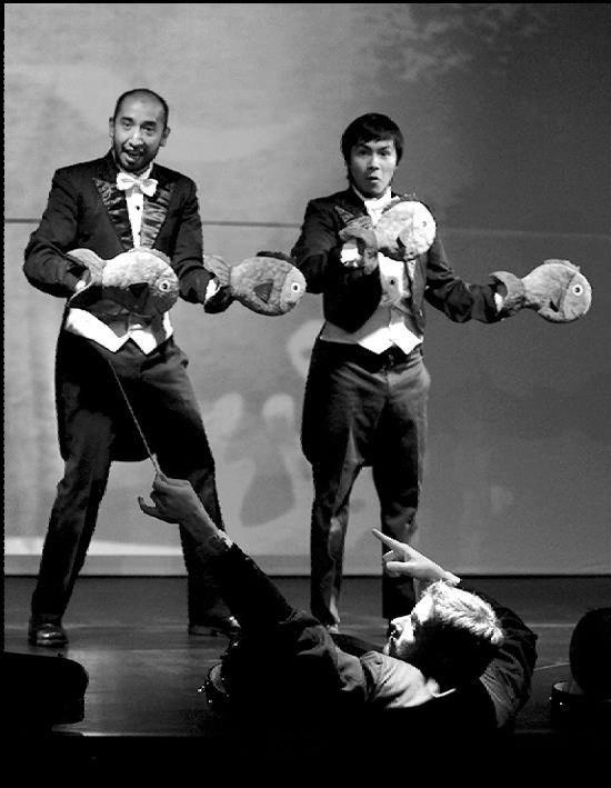 Black and white image.  Two men stand on a stage formally dressed in tuxedos with tales. They hold cut out fish shapes in their hands.  A man in the audience, with his back to the camera, stands and points to the left.