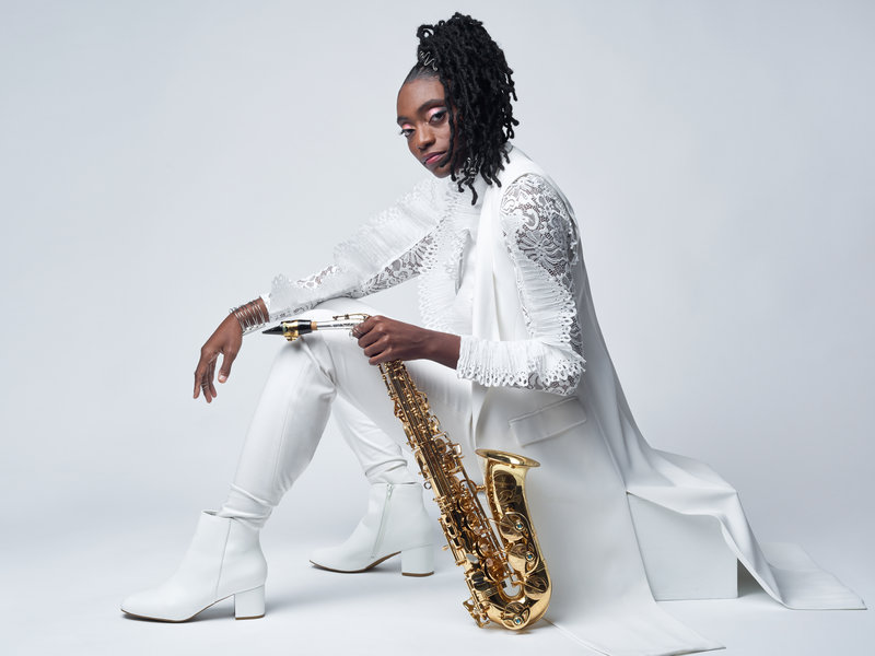Lakecia Benjamin sits on a low white block in left profile. She is dressed all in white with white boots.  Her saxophone rests on the floor beside her being help upright in her left hand.