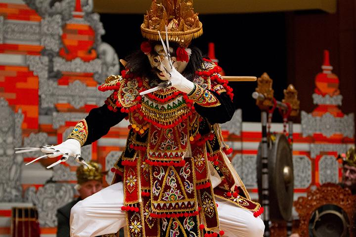 A dancer dressed in traditional Balinese garb strikes a pose in front of an ornate red and silver backdrop.