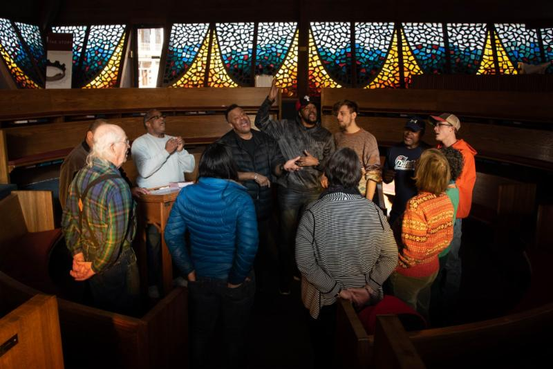Men and women stand in a circle surrounded by wooden pews and bright stained glass.  They are singing.