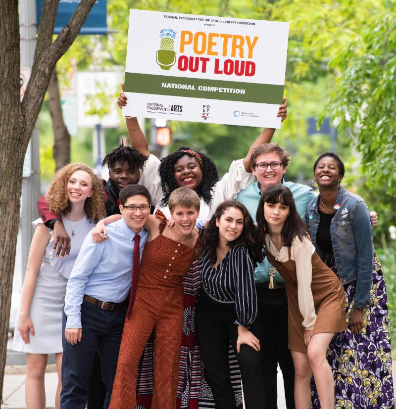 A group of nine young adults stands outside on a sidewalk - four in front and five in back.  The young woman in the center back golds a large Poetry Out Loud sign over her head. Trees frame the shot.