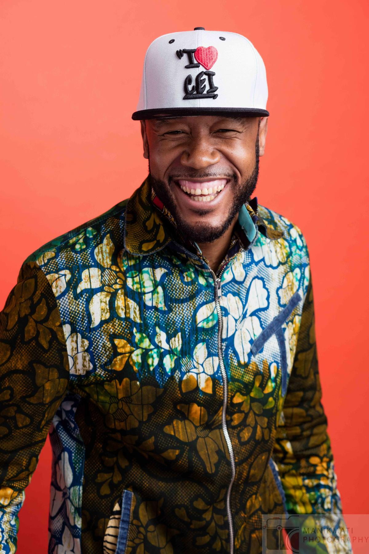 Vox Sambou is shot from the waist up against a salmon background. He is wearing a dark gold floral shirt and a baseball cap. Vox is a black man with a trimmed beard. He smiles at the camera.