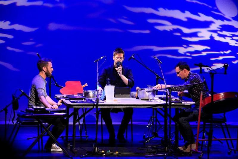 Three musicians are seated around a table onstage.  They have a variety of instruments and other sound making objects around them. The backdrop behind them is a vivid blue with white accents.