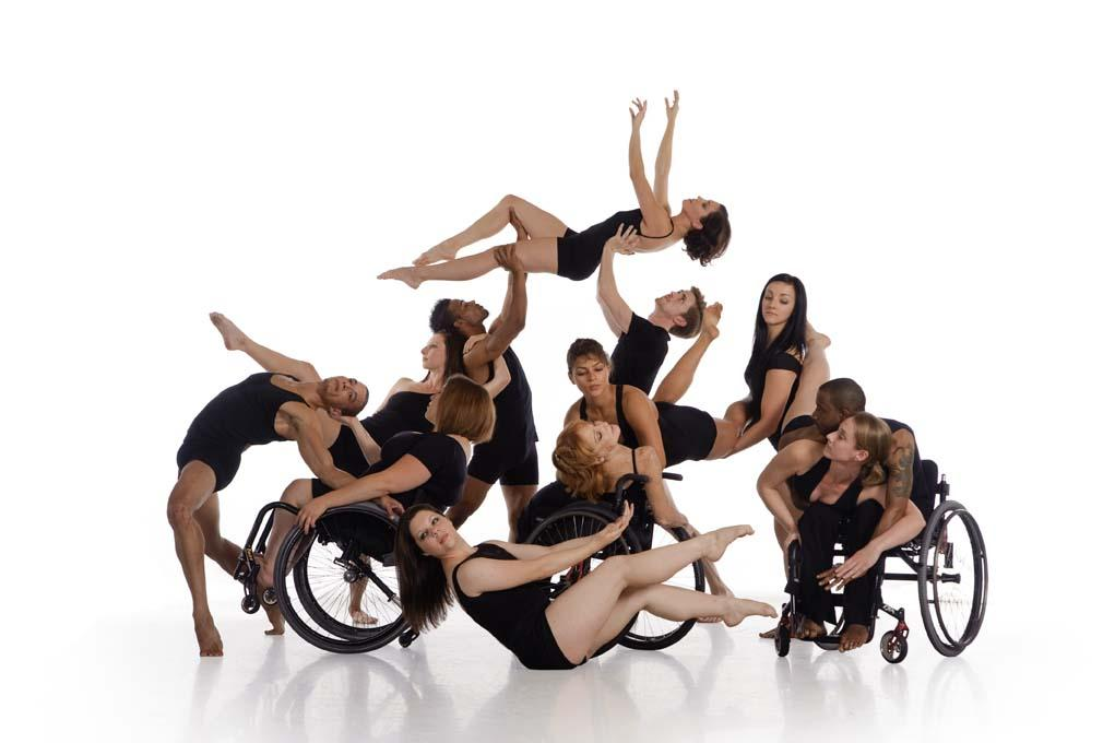 A group of dancers in black leotards pose in front of a white background.  Some of the dancers use wheelchairs and some do not.