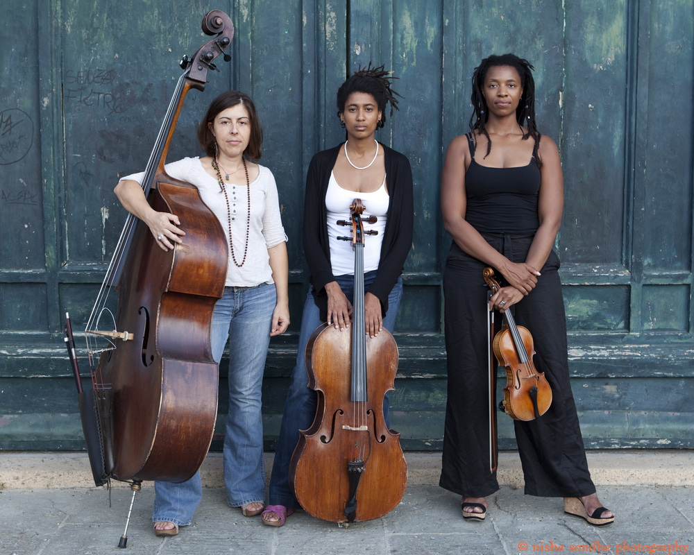 Three women holding stringed instruments stand in front of a faded blue wooden building.