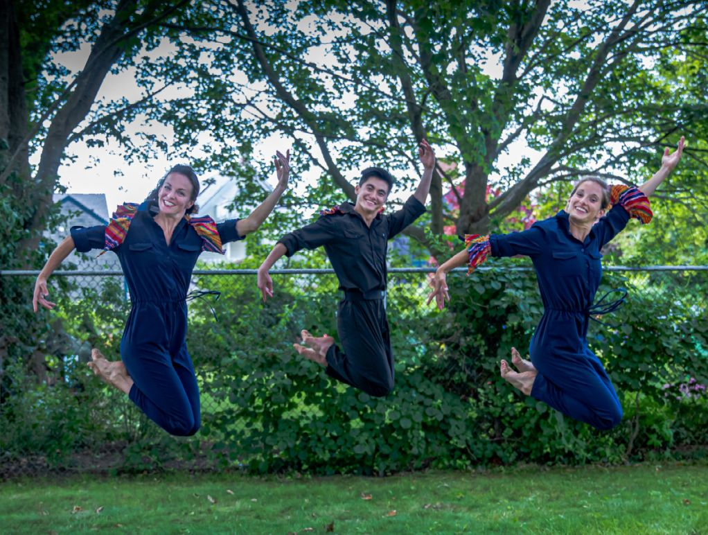 Three dancers wearing dark blue jumpsuits jump up with knees tucked and arms extended. They are on a grassy lawn with a chain link fence in the background.