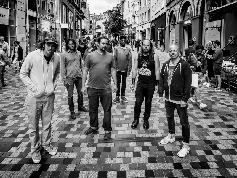 Black and white image of five casually dressed men standing in a European pedestrian street surrounded by buildings.