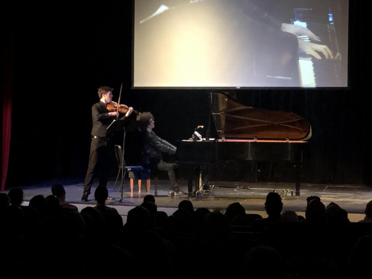 Shot from behind the audience, two musicians play on a dimly lit stage, a large screen behind them showing them performing in close up.  The musician to the far left stands playing the violin. Next two him a pianist plays a grand piano.
