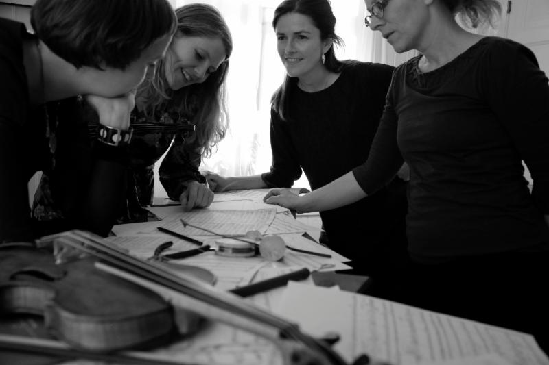 Image is in black and white. Four women in black clothing stand around a table.  Instruments and sheet music are spread on the table top.