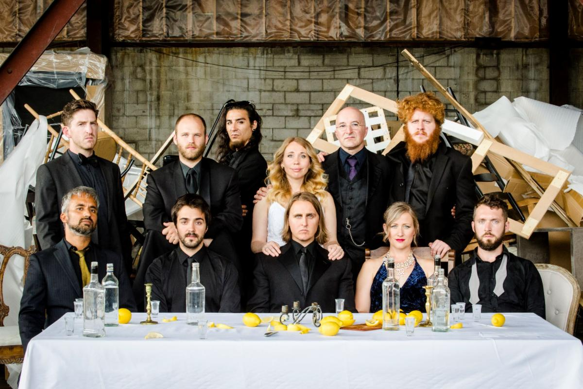 Two rows of musicians stand and sit behind a table covered with lemons