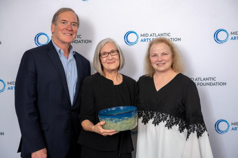 Three adults stand in front of a white backdrop with the blue and black Mid Atlantic Arts Foundation logo. Left to right: Alan Cooper, Former Executive Director of Mid Atlantic; Julia Olin, Alan Cooper Award Honoree; and Theresa Colvin, Executive Director.