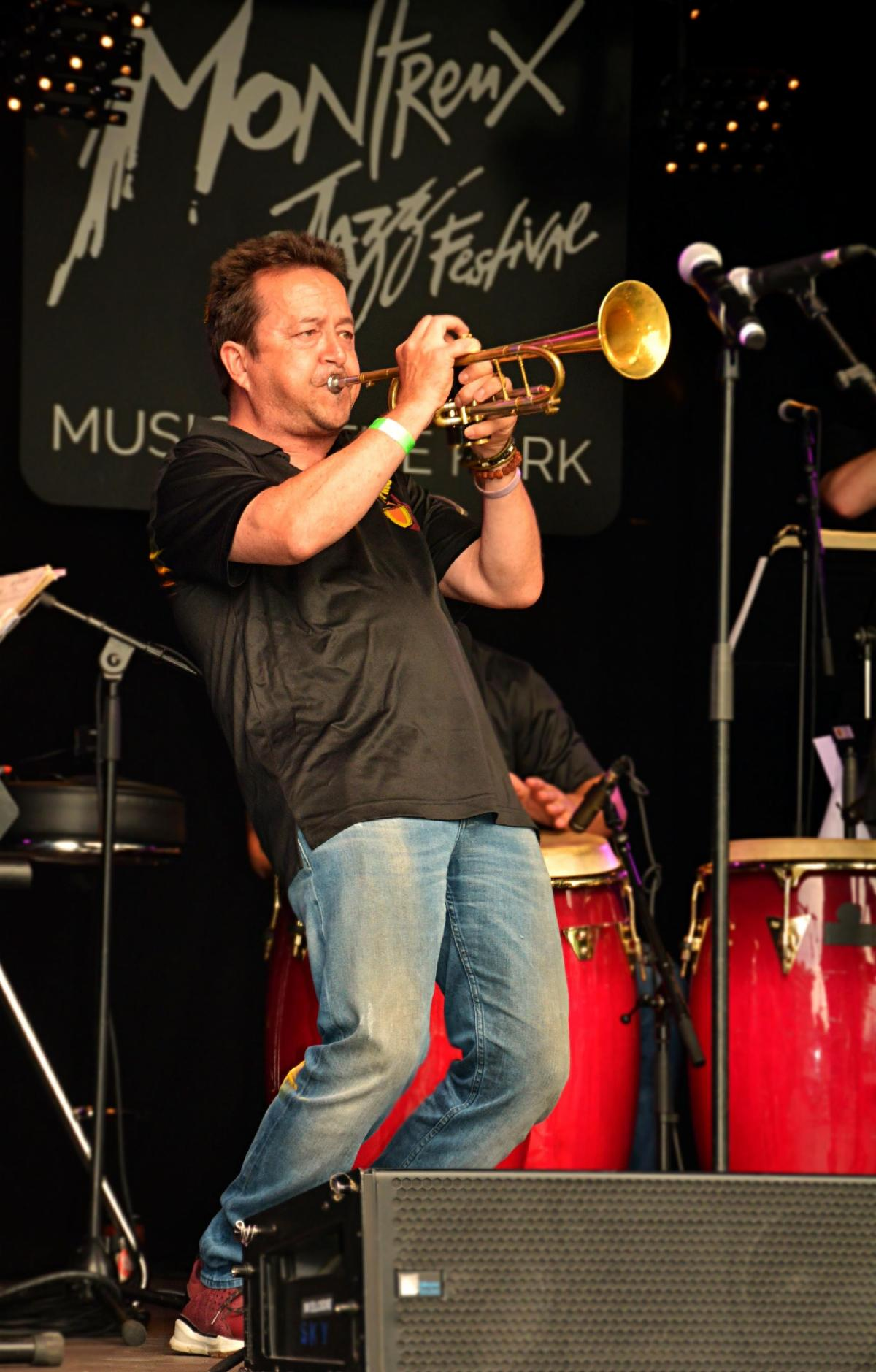 A man in blue jeans and a black shirt leans back as he plays the trumpet onstage.