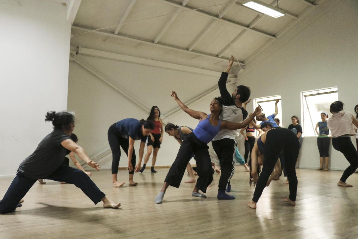 Approximately 20 dancers workshop a piece in a white studio with a light wood floor.  They all wear casual dance clothing and have bare feet.