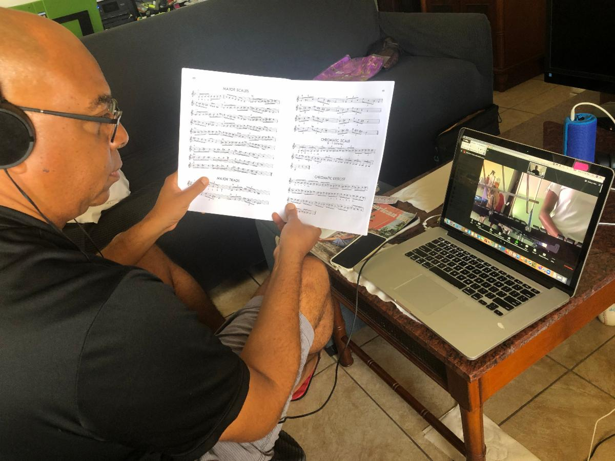 Dion Parson sits with his back to the frame left.  He is wearing a black shirt, headphones, and glasses and holding a piece of sheet music. On the laptop next to him, a student is having a virtual music lesson.