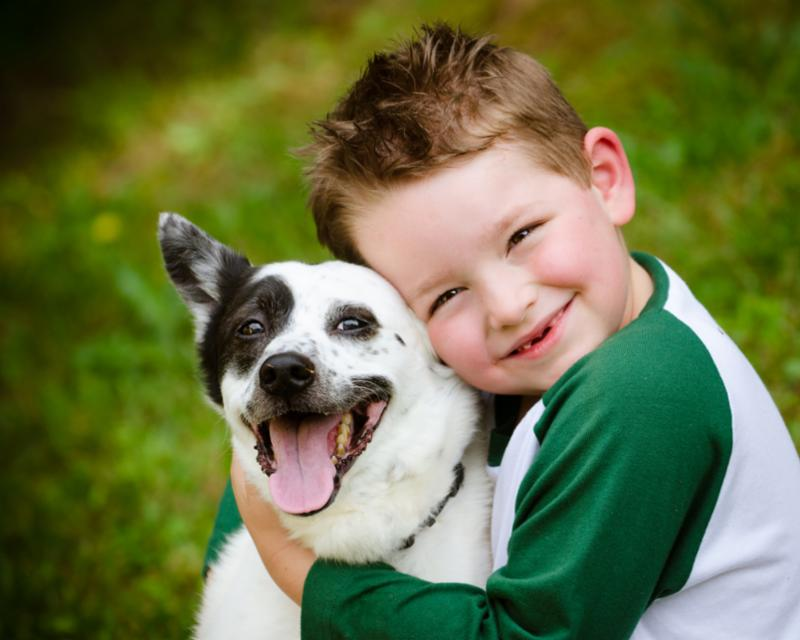 kid_hugs_black_white_dog.jpg