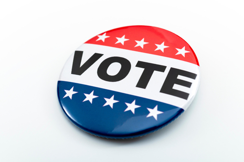 Democracy_ presidential election and voting poll concept with red_ white and blue vote glossy button pin with stars and stripes isolated on white background with clipping path cutout