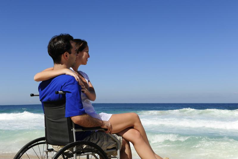 couple in love  woman and husband in wheelchair on the beach