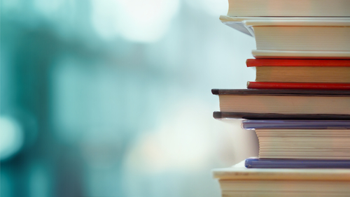 Book stack in the library room and blurred bookshelf for business and education background_ back to school concept