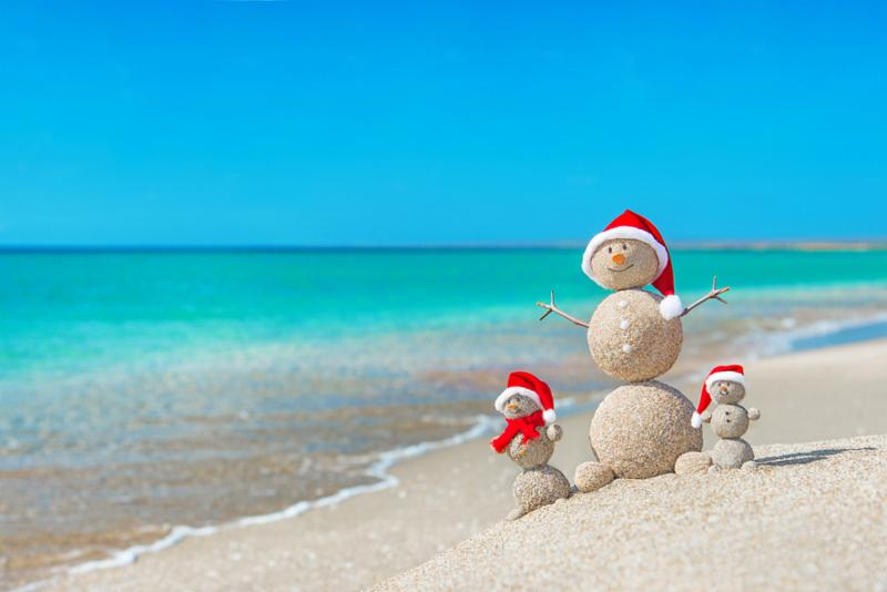 Snowmans family at sea beach in santa hats. New years and christmas holiday in hot countries concept.