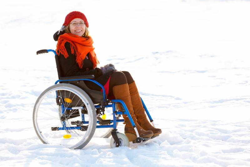 happy adult woman wearing winter clothes and sitting on wheelchair in the snow