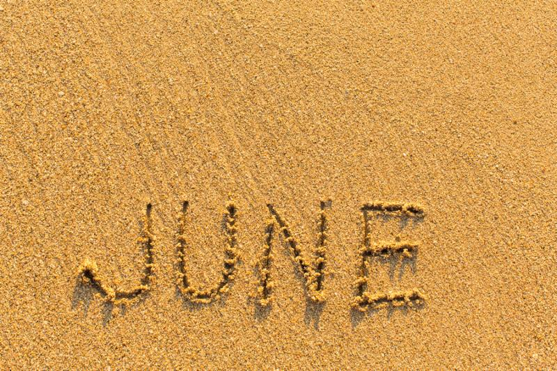 June - word inscription on the gold sand sea beach.