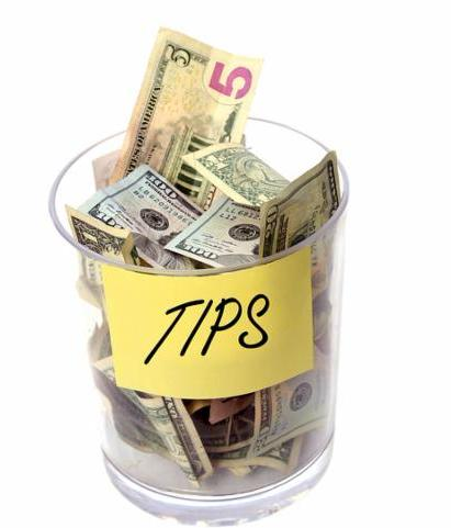 Tip Jar stuffed with money. Isolated on white with room for your text. Tip jar with sign. charity jar