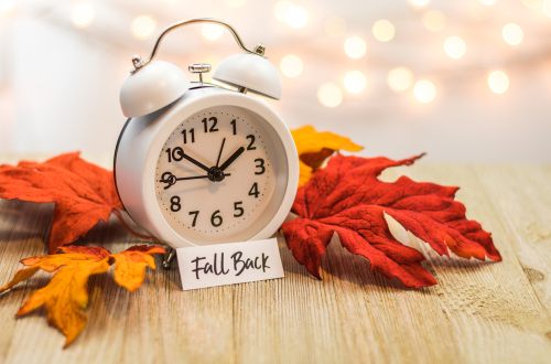 Fall Back Daylight Saving Time concept with white clock and autumn leaves_ soft bokeh background on wooden board