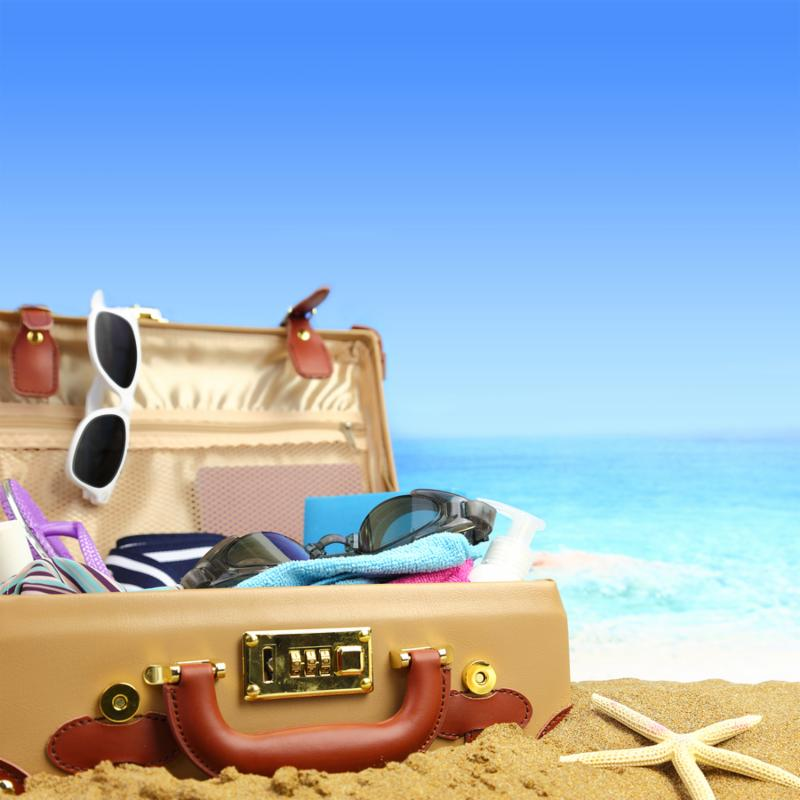 Full open suitcase on tropical beach background