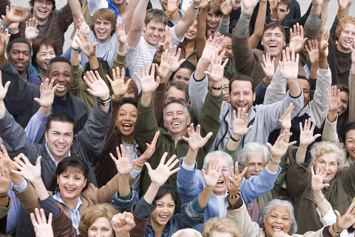 Multiracial group of people with hands raised in greeting