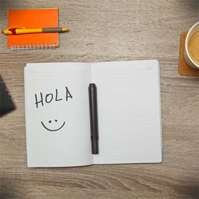 notebook with hola and smiley-face written in it