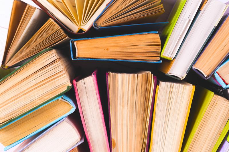 Open book_ hardback books on bright colorful background. Back to school. Copy space for text. Set of books in the library. Knowledge_ Science.