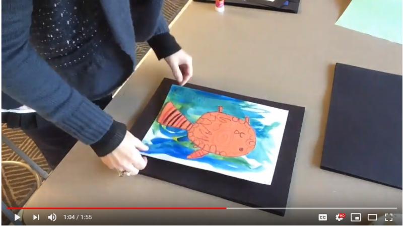 Preparing student painting for display
