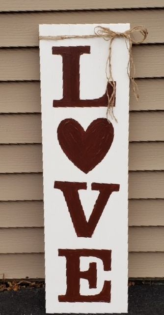 Vertical wooden sign with dark red letters spelling out the word LOVE with a heart for the O