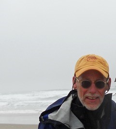 Photo of Philip with fog and ocean in the background.