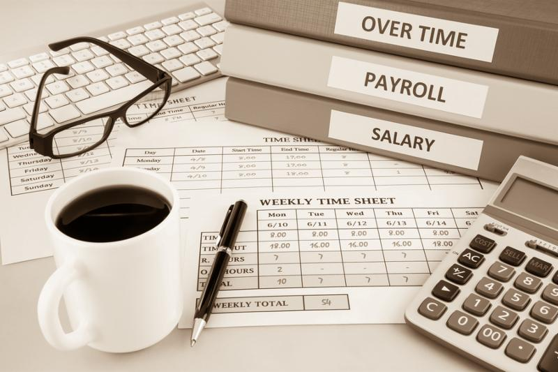 Human resources documents  payroll salary and employee time sheets place on office table with cup of coffee and calculator sepia tone