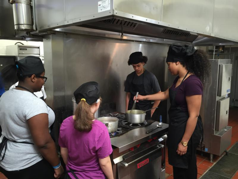 Photo from The Hospitality School Camp.  Students in the kitchen at the stove making lunch.