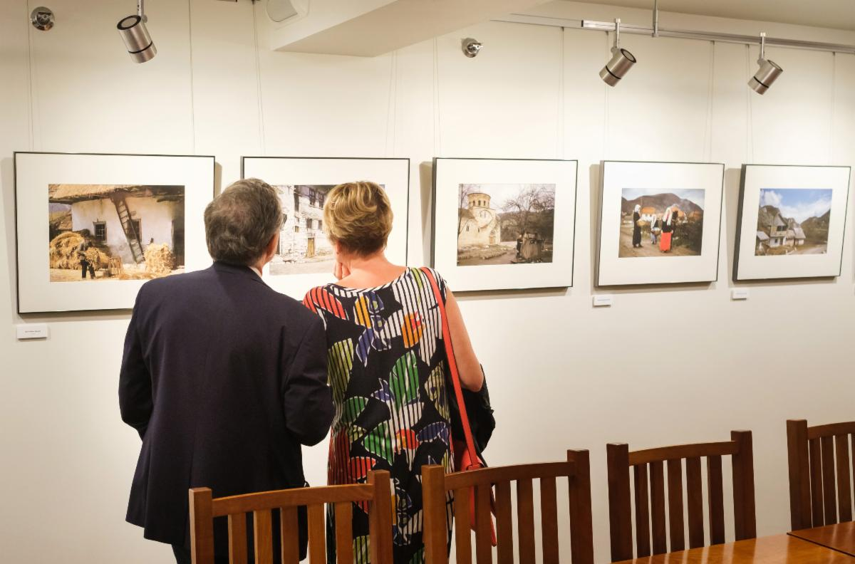 Man and woman viewing photos on a wall