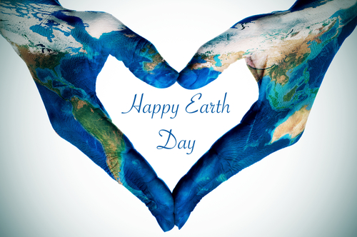 the hands of a young woman forming a heart patterned with a world map  furnished by NASA  and the text happy earth day